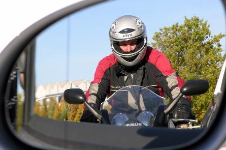 Blick in den Seitenspiegel auf einen Fahrschüler auf dem Motorrad.