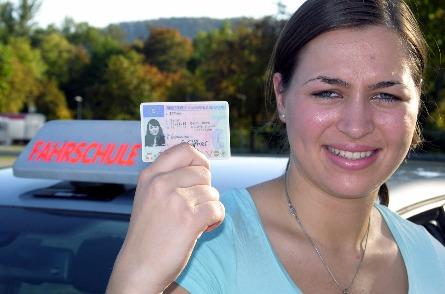 Schülerin zeigt nach bestandener Prüfung stolz ihren Führerschein.