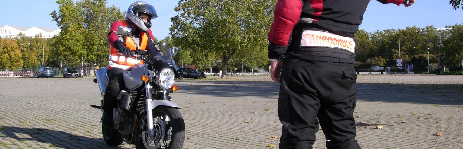 Motorrad-Fahrstunde auf einem Parkplatz.