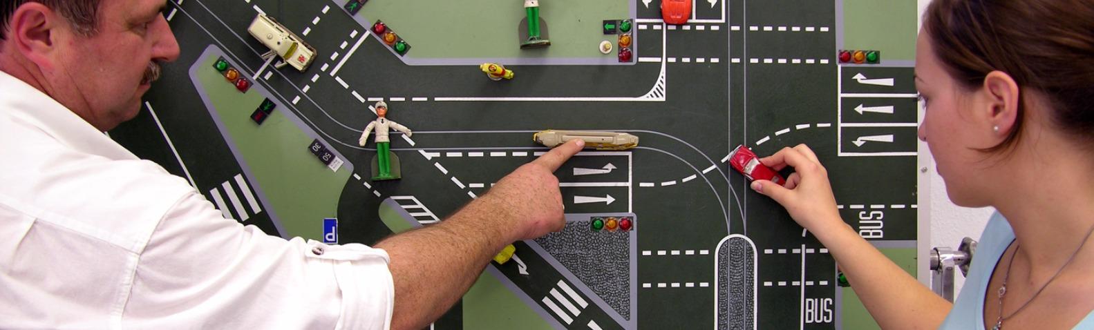 Fahrlehrer Roland Herter erklärt einer Schülerin an einer Tafel den Verkehrsablauf.