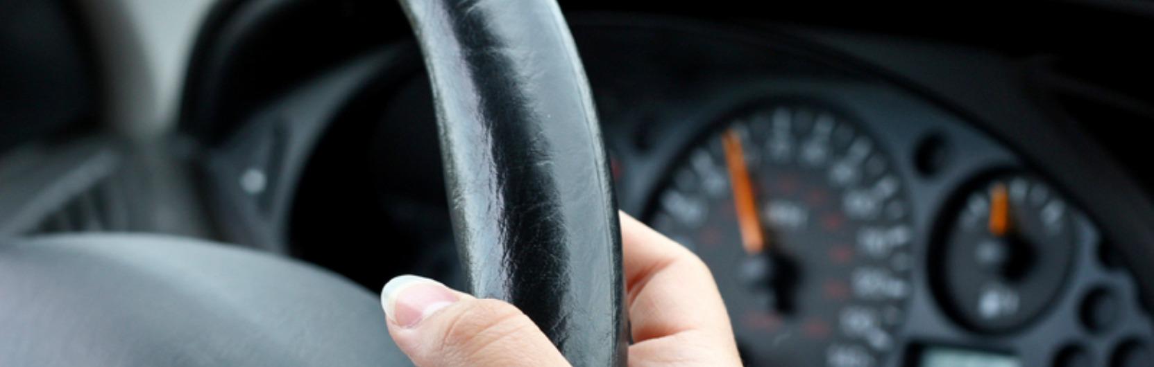 Nahaufnahme von einem Lenkrad und der Geschwindigkeitsanzeige in einem Auto.